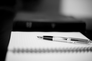 Grayscale closeup shot of a fountain pen on top of a notebook with a blurred background