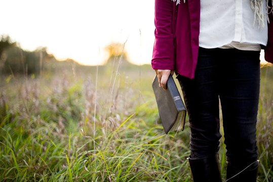 Closeup shot of a female standing in a grassy field while holding bible with blurred background