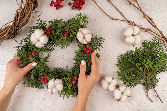 woman hands making DIY christmas wreath on wooden background top view