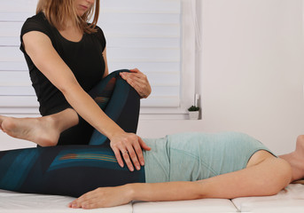 Physiotherapy treatment. Therapist treating injured knee of athlete female patient .