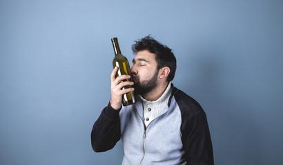 alcoholic; drunk man kisses a bottle of alcohol