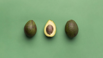 Avocado pieces on light green background, panorama