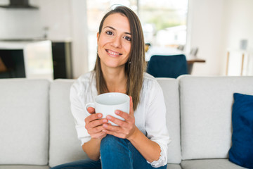 Brunette drinking a cup of coffee in the living room