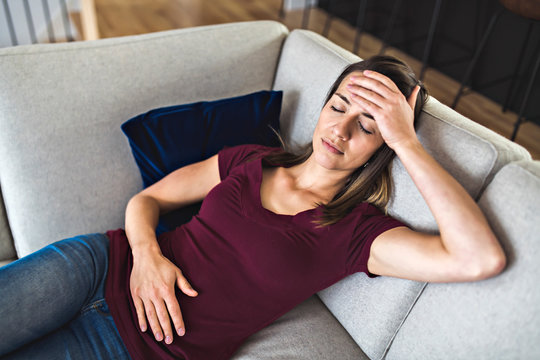A Sick woman lying on sofa in the living room with stomach ache