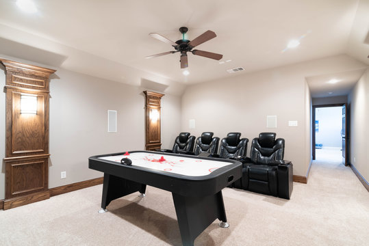 Traditional Media Game Room with leather chairs and air hockey table