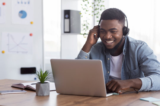 Black worker wearing headphones, watching webinar on laptop in office
