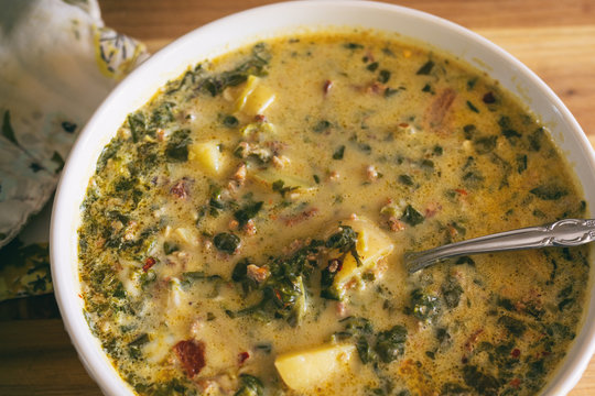 Close up view of a bowl of Zuppa Toscana, a hearty sausage stew that originated in Italy.