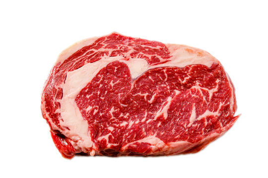 A rib eye steak of marbled grain-fed beef lies on a white background. Isolated.