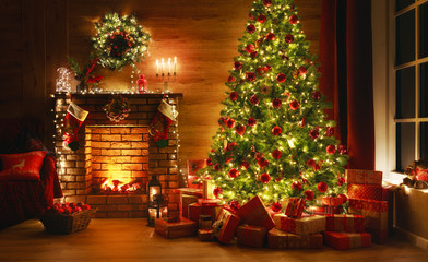 interior christmas. magic glowing tree, fireplace, gifts in dark
