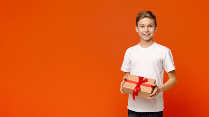 Smiling teenage boy with holiday gift box