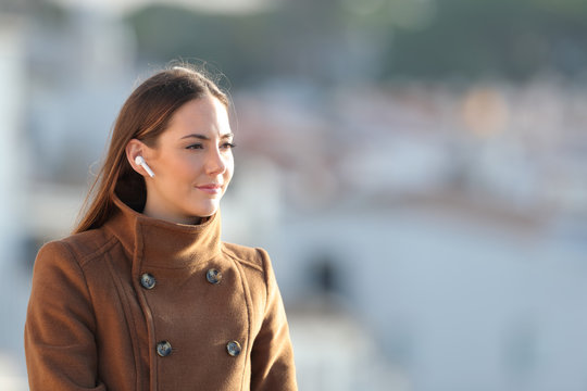 Relaxed woman listening to music using wireless earphones