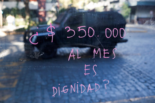 """A painted glass reading """"350.000 (Chilean peso) a month is dignity?"""" reflects an armored vehicle during a protest at Providencia, a wealthy neighborhood, in Santiago"""