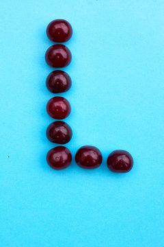 Letter L fresh cherry alphabet blue color flat lay
