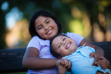 Little brother enjoying the company of his sister as he laughs with a joyful expression and holds her hand.
