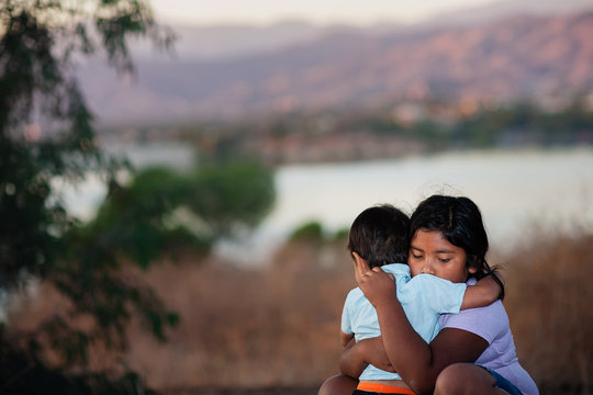 Brother and sister separated from parents are hugging each other in a foreign country, across a river.
