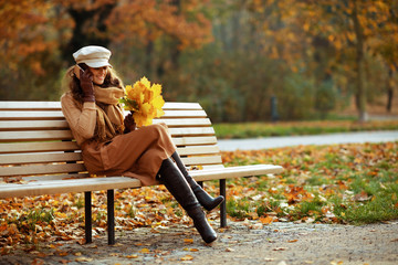 young woman with yellow leaves talking on mobile phone