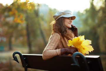happy stylish woman with yellow leaves speaking on cell phone