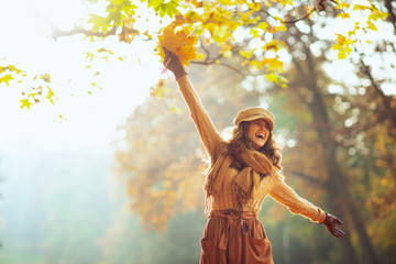 woman with yellow leaves having fun time outside in autumn park