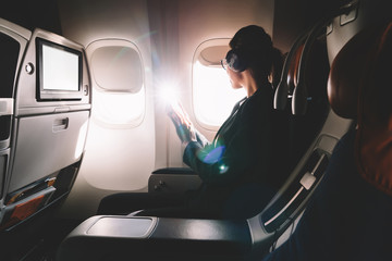 Female tourist in headphones listening audio book and looking in airplane window enjoying flight. Young 25 years old woman with cellular phone in hands sitting on seat during flight in first class