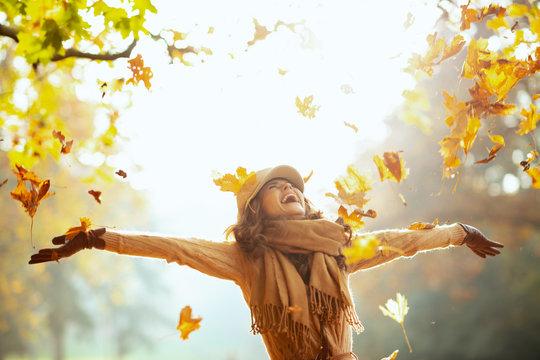 woman enjoying autumn and catching falling yellow leaves