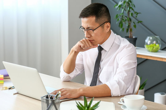 Asian businessman working on laptop in office