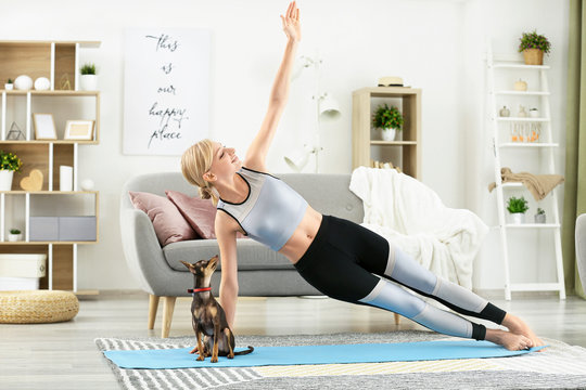 Beautiful young woman with cute toy terrier dog practicing yoga at home
