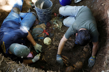 Members of the forensic team work at an exhumation site in the village of Yancolo as they search for human remains of the El Mozote massacre in the town of Cacaopera