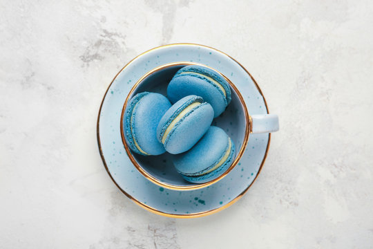 Cup with tasty macarons on white background