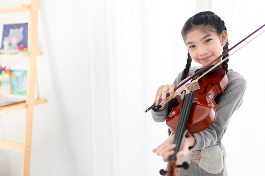 cute asian children holding violin on her shoulder and playing violin in her room, she feeling happy and smile in training time