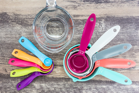Set of measuring cups, measuring spoons and  measuring glass use in cooking lay on wooden tabletop in in top view