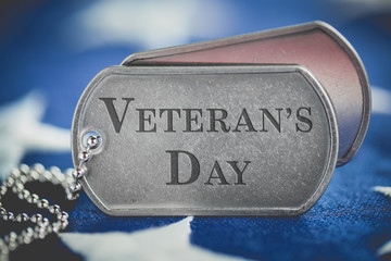 Worn US American dog tags on USA flag with Veteran's Day engraved text