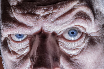 Close-up of the face of an elderly man. His wrinkled face forms light and shadow.