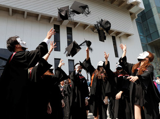 Graduates wearing Guy Fawkes masks throw their hats as they pose for their photo after a graduation ceremony at the Chinese University of Hong Kong in Hong Kong