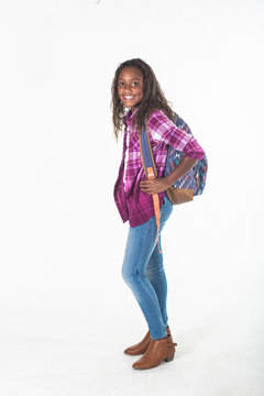 Smiling African American school girl isolated on white background. Wearing a backpack and a plaid jacket and ready to go to school. side view