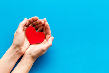 Heart icon. Paper heart in hands on blue background top view space for text