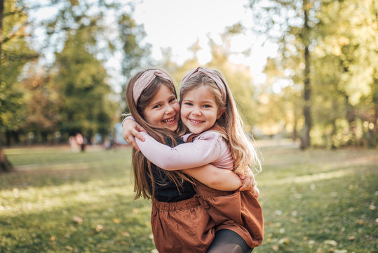 Two beautiful child sisters hugging in the park on a sunny day, portrait.