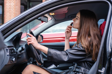 a young woman sitting in a car behind the wheel.she's going to go. woman paints her lips with lipstick and look in the mirror