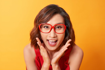 Image of screaming excited young cute woman posing isolated over yellow background.