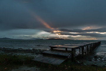 View of a pier on a lake, with a ray of sun against a moody sky