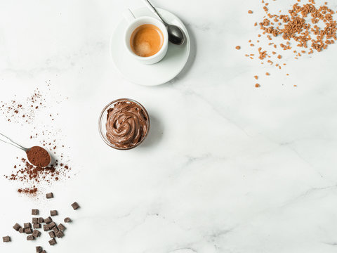 Sweet flat lay background. Chocolate, sugar, hazelnut cocoa spread, cocoa powder and coffee cup on white marble tabletop with copy space. Can use as mock up or special offer for cafe or confectionery