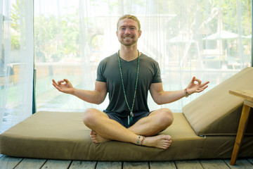 hipster guy practicing yoga . young attractive and happy athletic man sitting on resort bed in lotus pose doing meditation exercise smiling relaxed and zen like in harmony