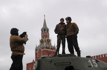 Participants take pictures on a tank after a military parade to mark the anniversary of a historical parade in Moscow