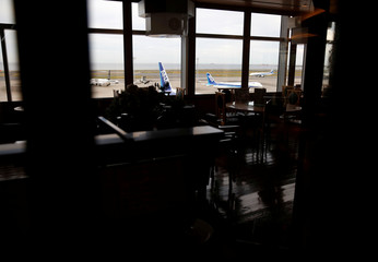 Airplanes are seen through a closed restaurant window during a water supply cutoff at Haneda Airport in Tokyo