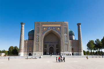 Tourists on Registan Square in front of Sherdor Madrasah in Samarkand, Uzbekistan