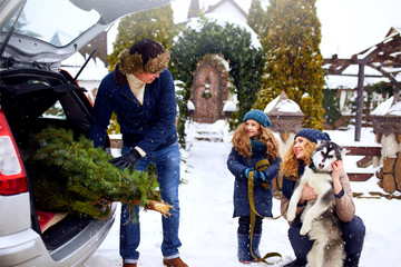 Father brought christmas tree in trunk of SUV car to daughter, mother and dog to decorate home. Family prepares for new year together. Large boot space concept. Snowy winter outdoors
