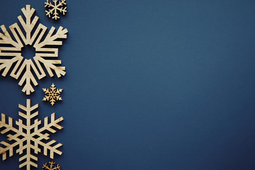 Blue Christmas background with handmade wood snowflakes in rustic style.Beautiful New Year wallpaper with empty space for text.Wooden hand crafts on poster template for winter holidays Fototapete