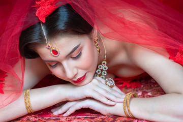 Beautiful portrait of young Asian woman in traditional Hindu red sari wedding clothes with bride dressed makeup and jewelery gorgeous brunette bride. Concept Indian costume