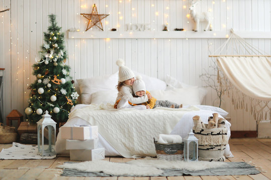 sisters are hugging on bed in Christmas interior