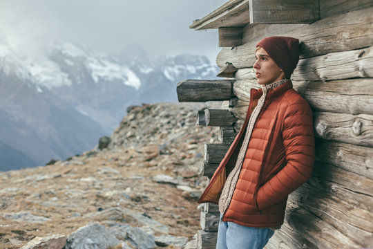 Handsome male model wearing warm sweater and winter coat over mountains with snow