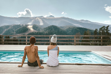Two people spending vacation in swimming pool with mountain landscape
